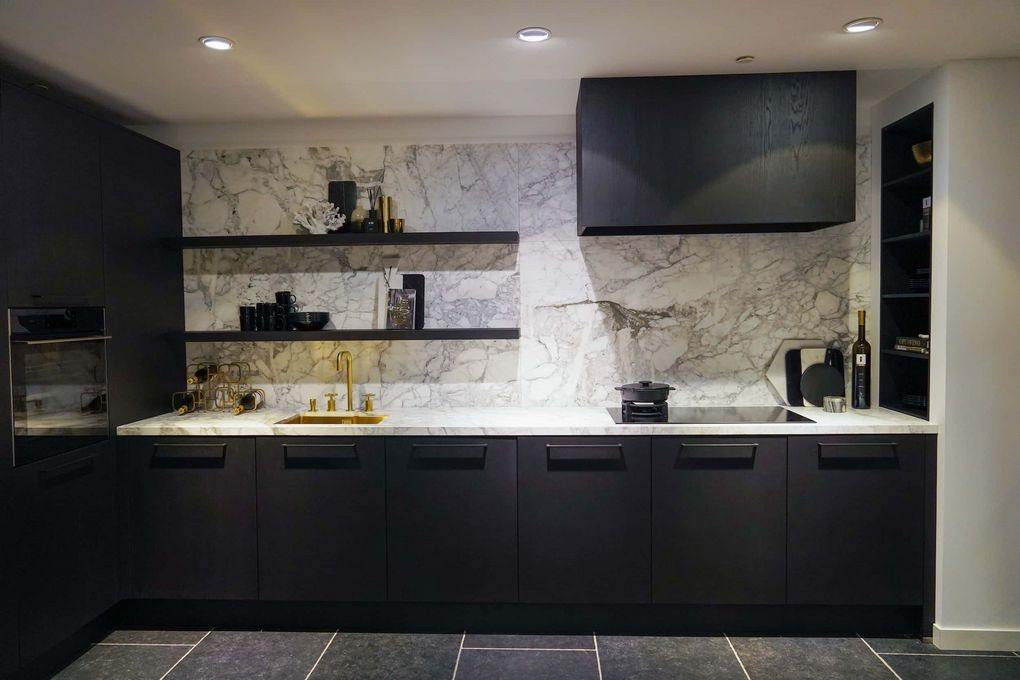 Zwarte l-keuken met marmer werkblad